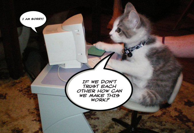 The image shows a kitten sitting on a little chair, talking to a computer. Trust