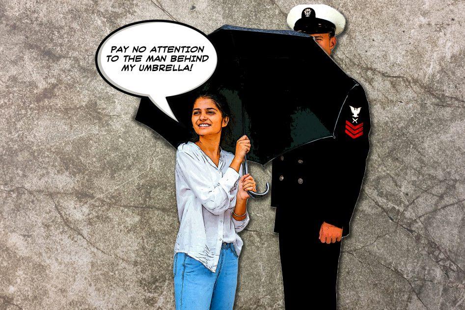 A milspouse hides her service member spouse behind an umbrella.